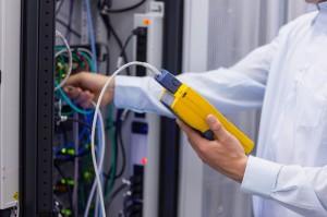 Technician using digital cable analyser on servers